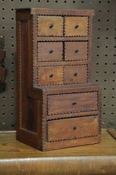 "Realized Price: $82 in 4/2013    Estimated Price: $100 - $200  Description: TRAMP ART MINIATURE STEP BACK CUPBOARD. American, first half of 20th century. Cigar box wood step back, six half drawers over two full, hook pulls, 13.5""h."