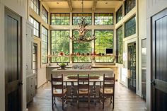 Incredible cabin style kitchen with ceiling height steel windows accented with a rustic wooden shelf over gray lower cabinetry topped with a light stone counter framing a stainless steel gas range.