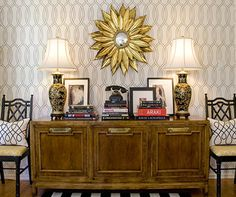 chair next to console table. stacked horizontal books, with art in the back