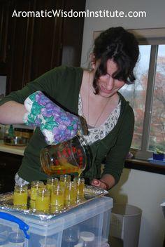 Kaley pouring body butter into glass jars.  www.aromaticwisdominstitute.com