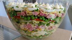 Laagjes salade. Ingrediënten: ijsbergsla, doperwten, tomaat, rode ui ,bieslook, bosui, hamblokjes, mais, oude geraspte kaas, komkommerschijfjes, gekookt ei, laagjes aanbrengen en tussen door calve slasaus en naturel dressing.