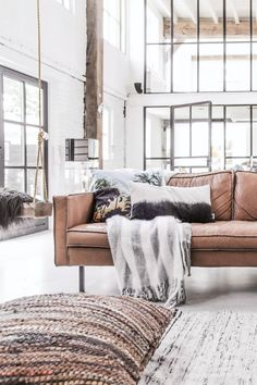 Ceiling-high loft windows are great when there is a lot of vertical space that light needs to fill. I love that they utilized white paint and floors to make the aesthetic more open and airy.