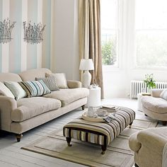 Neutral living room with striped wallpaper, neutral floorboards, neutral rug, neutral sofa and striped cushion