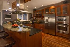 Open kitchen brown cupboard with fruit flowers and wine