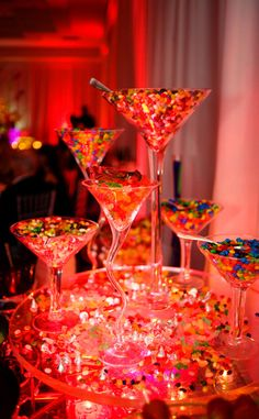 I like the idea of the uplit martini glasses filled with colored candies - more elegant than most of the candy centerpiece ideas on pinterest