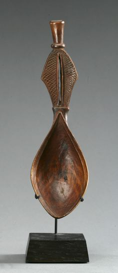 Africa | Spoon from Somalia | Wood; he bowl of deep foliate shape, the handle in the form of a stylized vagina with small truncated conical terminus.