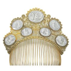 """CAMEO HAIR ORNAMENT,  SECOND QUARTER OF 19TH CENTURY. """"Set with seven carved shell cameos depicting mythological scenes, mounted within an open work foliate and scroll beaded surrounds, to a comb, inner circumference approximately 173mm."""""""
