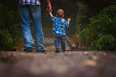 Father son pose for first birthday or 18 month old pictures. Walking across a bridge together