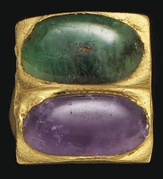 // A ROMAN GOLD FINGER RING   CIRCA 3RD-4TH CENTURY A.D.   The hoop flat on the interior, convex on the exterior, expanding to heart-shaped shoulders, supporting foliate prongs joined to a nearly square bezel, now set with an oval emerald cabochon and an oval amethyst cabochon  1 in.