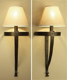 £189 Mitre wrought iron wall light. These stylish fittings have handforged tapered bands with rivet detailing to give the elegant mitre shape.  Standard bayonet bulb fitting. Price does not include shade.