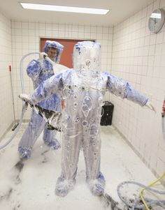 A doctor for tropical medicine and a nurse demonstrate the decontamination procedure as part of ebola treatment at Station 59 at Charite hospital in Berlin, Germany