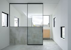 Entryway with black metal framed glass sliding door. House in Maniwa by Yasunari Tsukada. Photo by Takumi Ota.