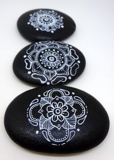 3 stones with white ink mandalas, sealed with a clear gloss spray. 2 1/2 to 3 inches long. The stones are water resistant but intended for indoor