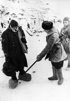 Soviet soldiers examine the straw winter boots worn by a prisoner at Stalingrad.