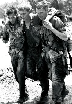 A wounded 199th LIB soldier is assisted by comrades, 1967.