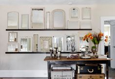 This pretty hodgepodge of white-framed mirrors in different shapes and sizes has been transformed into unusual wall art, propped on two slim picture shelves.