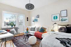 biala sofa,turkusowe dekoracje iczarne detale w salonie z łóżkiem - Lovingit.pl