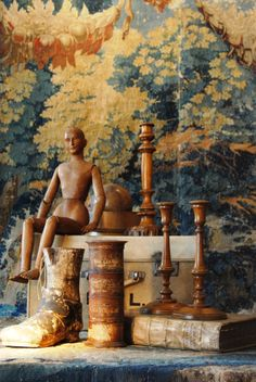 Verdure tapestry hanging behind beautiful hand carved objects.