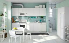 A sunny white kitchen with white dining table and chairs.
