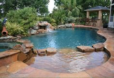 This is a beautiful backyard with many amenities and some special custom features. In the foreground is a sun shelf that is mostly enclosed creating an excellent place for very small children to enjoy the pool with a parent blocking the way to the deeper water. It is also a very visually appealing feature that…