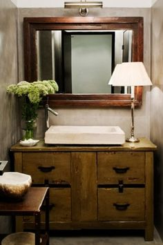 powder room . old cabinet . mirror with lamp above .