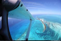 A view down onto North Cat Cay just about 50nm off the east coast of Florida. Taken from the inside of the aircraft through the huge cockpit windows of this Cessna. Bimini island can be seen just to the north being to first and closest port of entry...