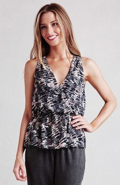 Paper Crown flirty peplum tank with elastic waist. Length hits at high hip. V-neck cross over in front. Dry clean only. 100% Polyester.