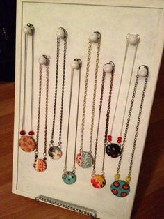 Necklace display made with cork bulletin boar, wooden knobs, and paint. Can hang or prop on easel. Directions.