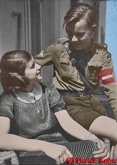 A young boy of the Hitler Youth organization enjoys a chat with a girl during a warm summer day in the Reich.