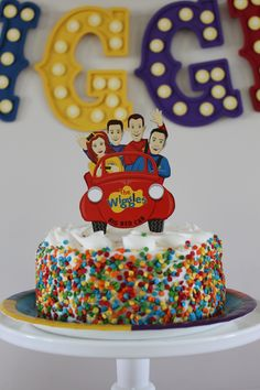 Featured Kids Party Themes Bright sprinkles and a cake topper featuring The Wiggles elevates a cake with fluffy white frosting to an easy DIY masterpiece worthy of your little one's star-studded Wiggles birthday party celebration.