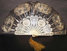 This antique Victorian era lithograph foil inlay pierced flirting mirror fan dates from the 1850s. It is made of pleated embossed silver foil and black paper with raised rococo design accents, cupids and hand colored painted lithographs. There are vignette medallion prints on both sides of early 1800 peasant scenes, with ladies, gentlemen, children and dogs. There are elaborate intricately carved and pierced bone sticks and guards, with silver foil inlay accents, etched floral designs and a…