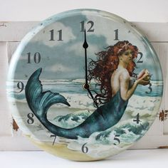 Gorgeous accent piece for any coastal or nautical themed room, this metal, full-functioning, battery-operated clock features an elegant sea beauty mermaid holding a conch shell and adorned with a starfish in her flowing red hair.