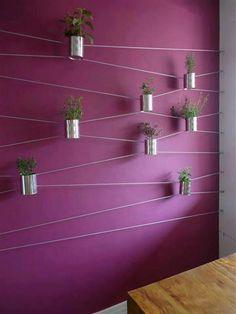 Pared decorada con cables y maceteros hechos con latas.