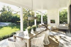 The covered porch off the family room is one of the house's most used spaces and the site of dinners and parties year-round. Varaschin's Tibidabo chairs surround a teak Parsons dining table from Restoration Hardware. Above is Marset's Soho outdoor pendant from YLighting.