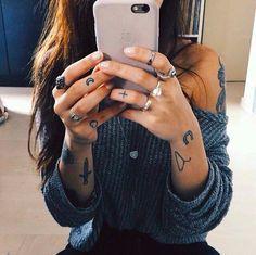 Chica sacándose una foto frente al espejo, lleva tatuajes pequeños en brazos