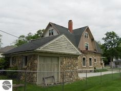 Stone garage of a home built in 1917 at 123 W. End St. in Alma, Michigan. Asking price $144,900. The 3 story home features 2,912 sq. ft., 6 bedrooms, 2 bathrooms, stone exterior, built-in bookcase, foyer, formal dining room, den/study, fireplace, hardwood floors, beamed ceilings, original woodwork, beveled glass pocket doors, double-decker glass enclosed porches overlooking backyard, large updated kitchen with island, 10 x 16 bonus room on 3rd floor, detached garage and 6,970 sq. ft. lot.