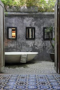 an outdoor bath tub and bathroom make with a walled yet open roofed room! Heart eh rug and stone floor