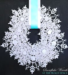 ^Snowflake wreath - Supplies:    Two packs of large Dollar Tree Snowflakes  Two-Three  packs of medium Dollar Tree Snowflakes  Hot Glue Gun  Ribbon for hanging