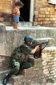 Fake - A completely fake photo of a little boy peeing on the head of a US soldier (who in some versions of this image has a US flag on his helmet). - The problem is the picture is not of US soldier at all. It is almost certainly a an Israeli soldier (you can see the Galil rifle).