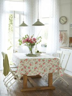 Retro Romantic dining room design. Light curtains from floor to ceiling, wood table with floral table-cloth and silver pendant light.