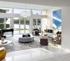 Brown Davis custom designed the room's handmade silk rug to reflect the movement of Biscayne Bay, which is seen through a wall of glass. A vintage chandelier by Barovier and coffee table by Scala Luxury complete the space.