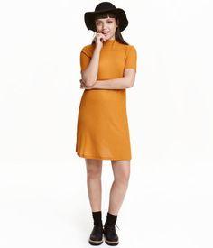 Sennepsgul. Kort kjole i A-facon i blød jersey. Har lav rullekrave og korte…