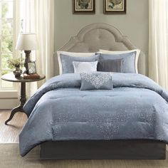 The Madison Park Eliza Comforter Set mixes a modern with contemporary. This woven collection features a dusty medium blue base with dark grey and silver scrollwork woven into the base.