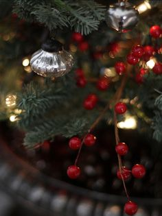 Dress the tree with jingle bells. Mix in silver ornaments and winterberries for a classic Christmas tree theme.