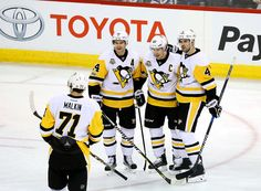 Jets vs. Penguins - 03/08/2017 - Pittsburgh Penguins - Photos : Evgeni Malkin #71 of the Pittsburgh Penguins joins teammates Chris Kunitz #14, Sidney Crosby #87 and Justin Schultz #4 to celebrate a second period goal against the Winnipeg Jets