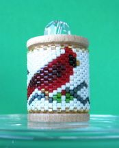 """Cardinal (Vertical) Spool Ornament at Sova-Enterprises.com Decorate a wooden spool with a band of peyote stitch beads. Included in this full color design is a dated pattern, an undated pattern, a pattern of the numbers 0-9 for year conversion, and a chart of recommended Delica beads. Pattern only, for FREE Spool Ornament Instructions see model #13393. The spool size is 1 3/16"""" x 7/8"""". Spools are available at Sova-Enterprises.com."""