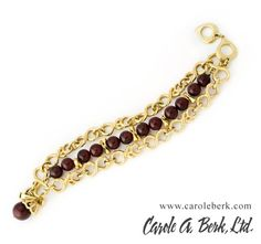 Yves Saint Laurent, signed in script, 80's gold tone chain link and cranberry glass bracelet.Bracelet consists of 3 rows, 1 1/2 in wide, 9 inches long