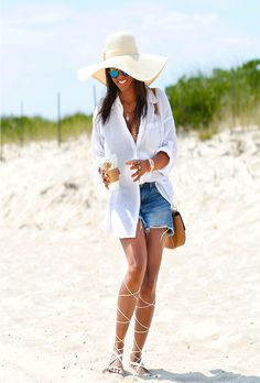 A roundup of the best blogger beach style for summer fashion inspiration | menswear button down as a cover up with cutoff jean shorts, straw hat, and lace up sandals