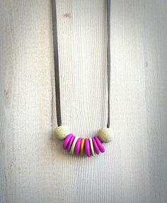 On a long dark brown and a soft leather cord there are handmade polymer clay beads. It makes it a simple and minimalistic jewelry, a nice gift for