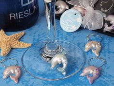 """Our oceans of love dolphin wine charms are the perfect compliment to your beach theme event. Each  wine charm is a resin Jumping dolphin shape design attached to a metal ring accented with clear beads, and are accented each with a different color glistening rhinestone. Each set contains four different colored dolphin design charms and measure 2"""" x 1"""" each. #timelesstreasure"""